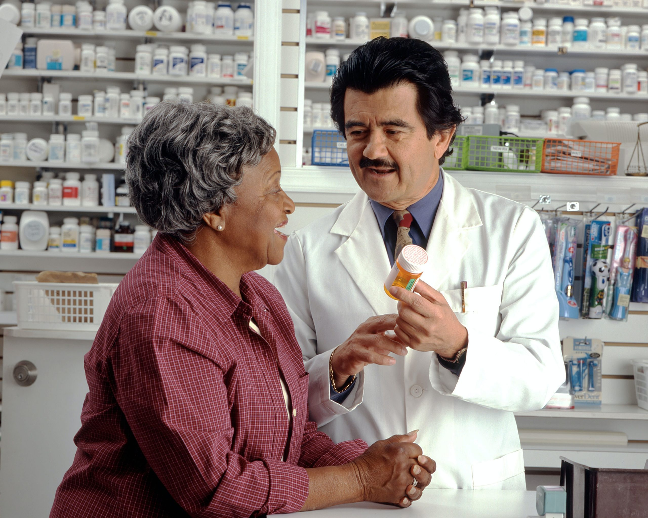 Pharmacist holding a bottle of tablets and talking to a customer